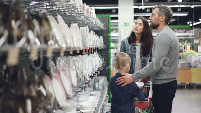 Maken och frun väljer plattor i redskapavdelning i supermarket, deras lilla son hjälper dem buying lager videofilmer