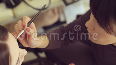 Makeup artist applies eye shadows on eyes of model. Makeup artist applies eye shadows on eyes of the model stock video footage