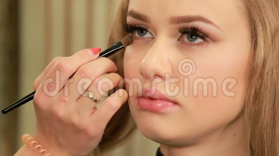 makeup artist applying eyeshadow on eyelid of a female