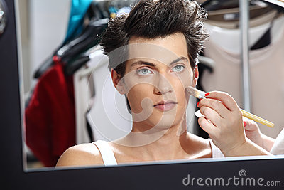 Makeup artist applying foundation with a brush, man in the dressing room mirror Stock Photo