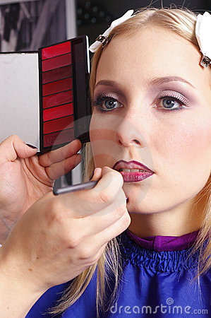Makeup artist tracing red lipstick on the lips
