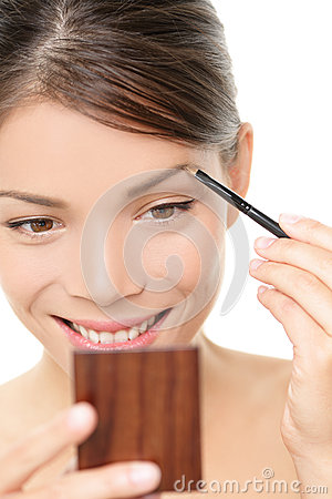 Makeup girl putting eyebrow color in mirror