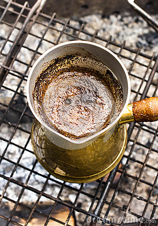 Making espresso coffee in vintage coffee pot on a grill bar outd