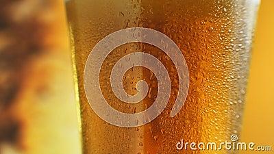 Makro-Schuss feiner Blasen, die in einem Glas mit orangefarbenem Flüssigkeit aufsteigen Cold Light Beer in einem Glas mit Wassert stock footage