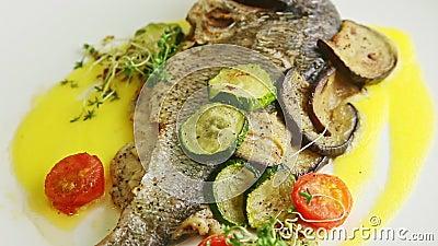 Makro-Sicht auf den ganzen gebackenen Fisch mit Gemüse, das sich um sich dreht stock video footage