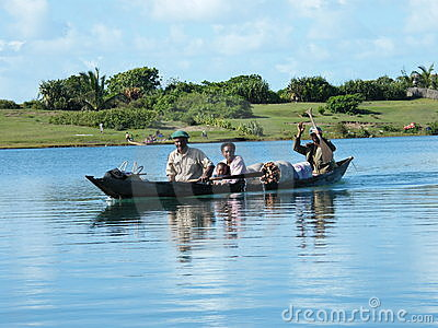 Malagasy family crossing river by canoe Editorial Photo