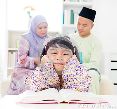 Malay girl reading book.