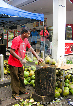 Free Malaysian Man Cutting Young Coconuts Stock Photography - 71032032