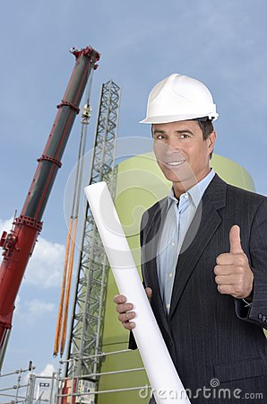 Male architect at construction site smiling and thumb up
