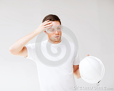 Male architect in safety glasses taking off helmet