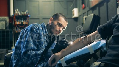 Male artist in the process of making a tattoo in his salon. 4K stock footage