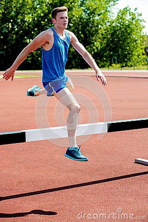 Male athlete jumping hurdle