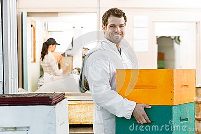 Male Beekeeper Carrying Stack Of Honeycomb Crates