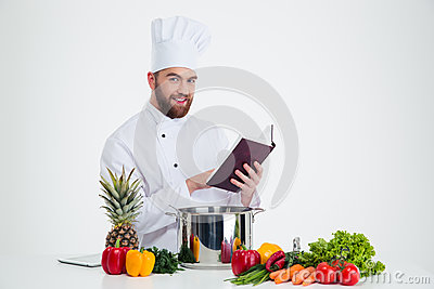 Male chef cook holding recipe book and preparing food Stock Photo
