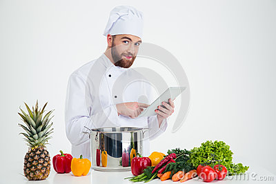 Male chef cook using tablet computer while preparing foo Stock Photo