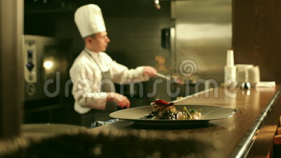 Male Chef is Cooking Flambe in Restaurant Kitchen. Male chef is cooking flambe meat in restaurant kitchen. Ready-to-eat dish is standing on the counter in the