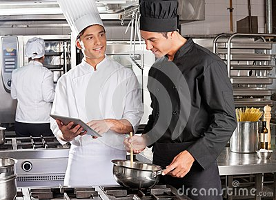 Male Chef Assisting Colleague In Preparing Food