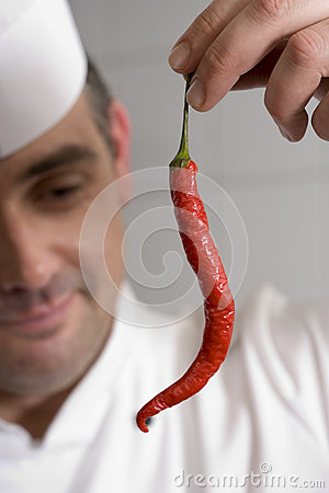 Free Male Chef Examining Single Red Chilli Pepper In Commercial Kitchen, Smiling, Close-up (differential Focus) Stock Photo - 41720250