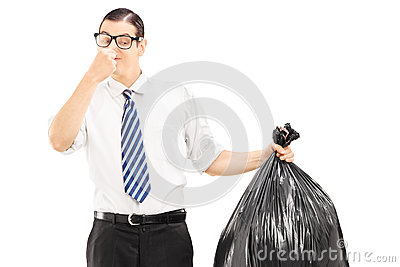 Male closing his nose and holding a stinky garbage bag