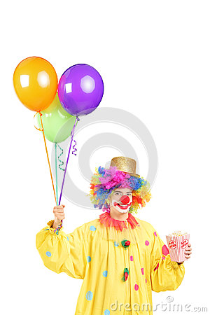 Male clown in costume holding bunch of balloons and popcorn box