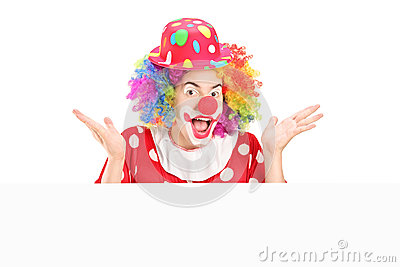 Male clown gesturing behind blank panel