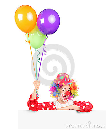 Male clown wqith balloons posing behind panel