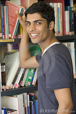 Free Male College Student Reaching For A Library Book Royalty Free Stock Photography - 5949597