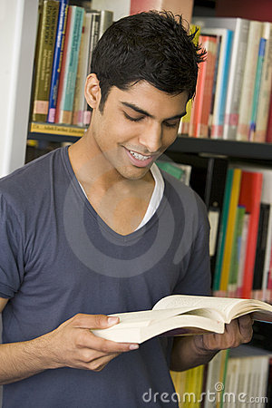 Male college student reading in a library