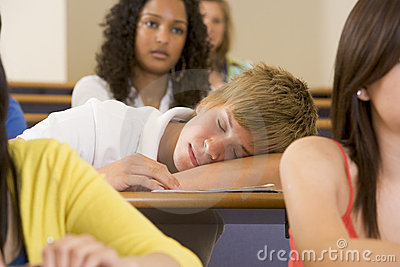 Male college student sleeping through a lecutre
