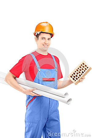 Male construction worker holding a brick and a blueprint