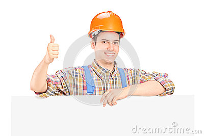 Male construction worker posing behind a panel