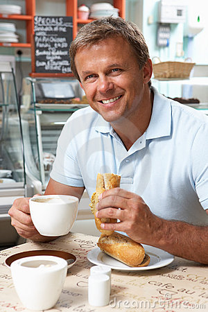 Male Customer Enjoying Sandwich And Coffee In Cafe