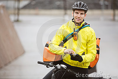 Male Cyclist With Courier Bag Using Mobile Phone