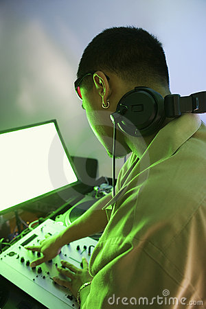 Male DJ using mixing equipment.