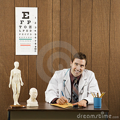 Male doctor at desk writing.