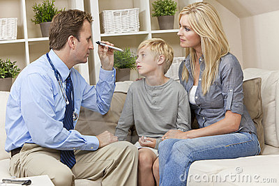 Male Doctor Home Visit Examining Child With Mother