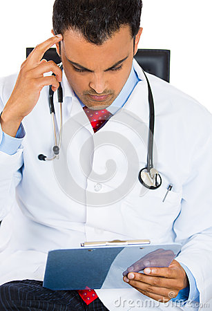 Male doctor in lab coat holding reading Patients Chart while sitting on a chair