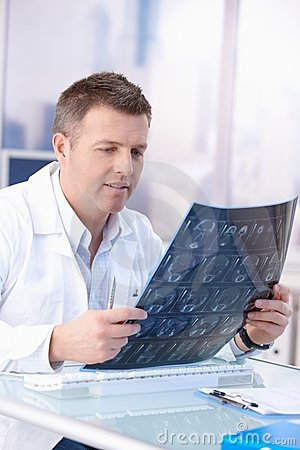 Male doctor looking at x-ray image in office