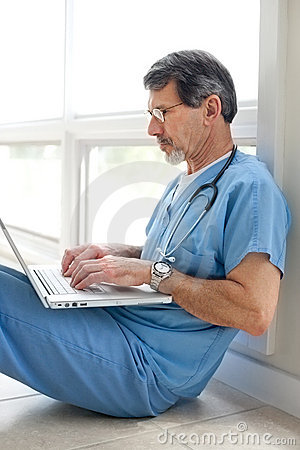Male Doctor or Nurse seated with Laptop Computer