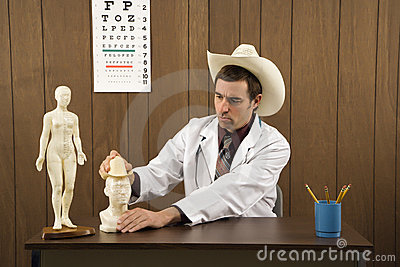 Male doctor wearing cowboy hat playing with figurine.