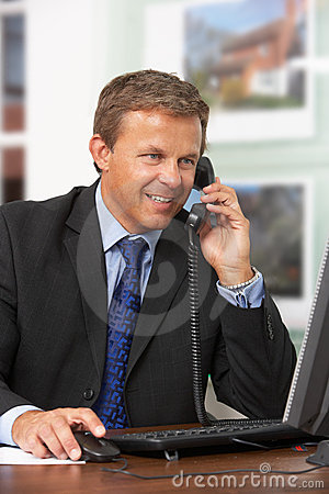 Male Estate Agent Talking On Phone At Desk