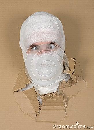 Male face on bandage in carton hole