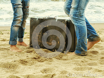 Male and female feet on the sand near the sea with a leather suitcase