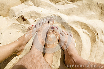 Male and female legs entwined in the sand on the beach