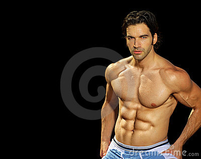 Male fitness model on black background