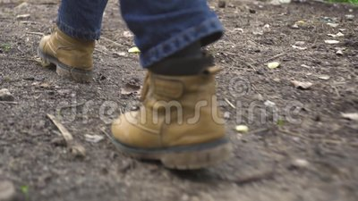 Male foot in shoes walking on countryside road back view. Man in shoes from beige leather walking on footpath, low angle. View stock footage
