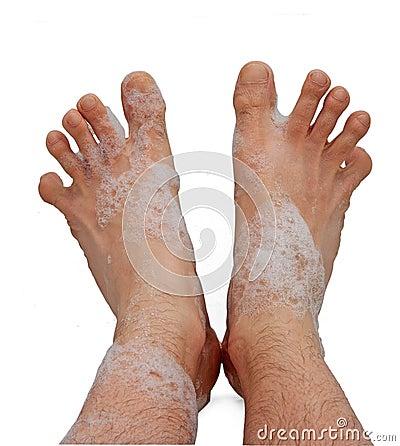 Male foots in bath foam
