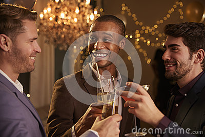 Male Friends Make Toast As They Celebrate At Party Together