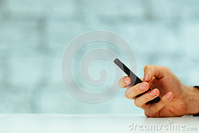Male hand typing on smartphone
