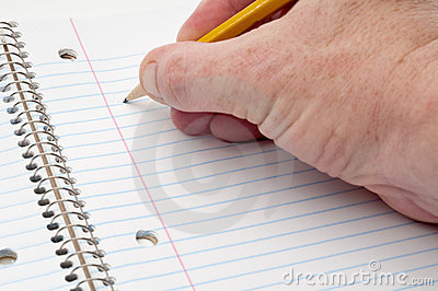 A male hand writing on lined notepaper